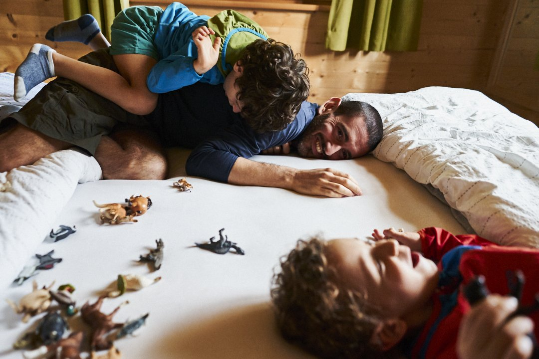 Papà che gioca sul letto con i suoi due figli. Il gioco che stanno facendo sono dinosauri in miniatura. Il grande dei due è salito in spalle al papà che se la ride. Il piccolo anche lui sta ridendo. Il bello del reportage è il potere di fermare i nostri ricordi di vita reale.