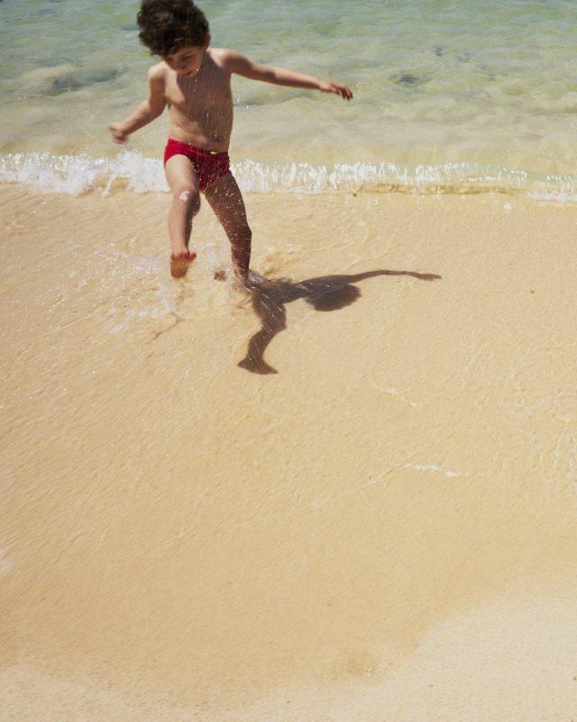 Bambino in vacanza a Fuerteventura schizza l'acqua in riva al mare