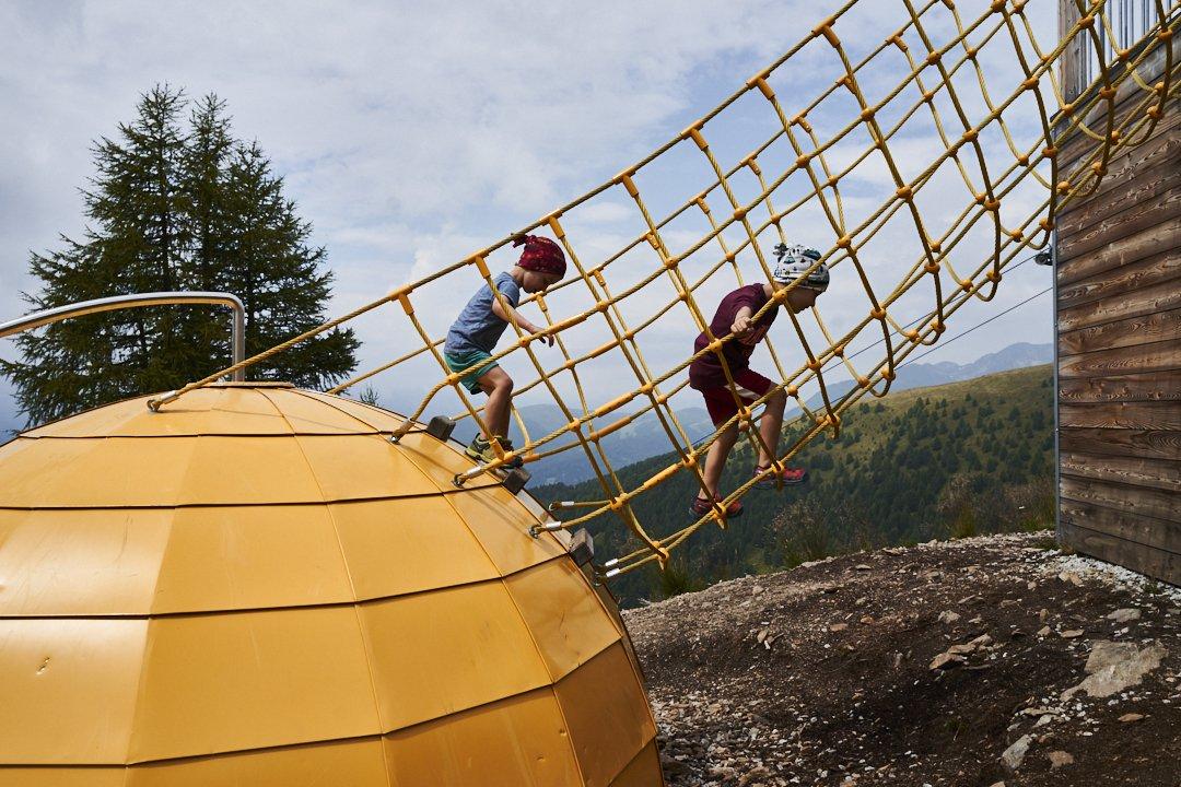 Due fratelli in montagna che si arrampicano su una rete