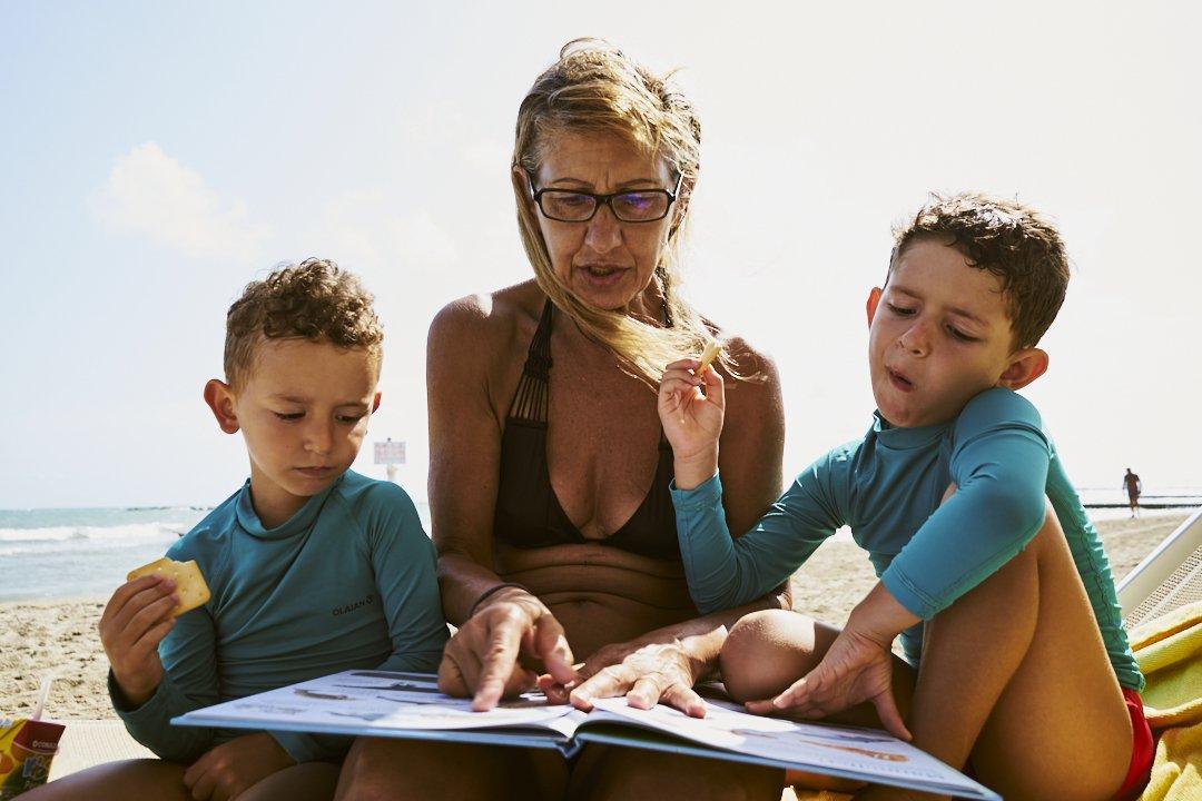 La nonna legge un libro ai nipoti in spiaggia
